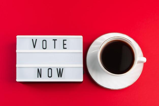 Votez maintenant. signe et tasse de café sur un rouge