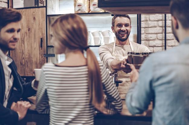 Votre café est prêt ! vue arrière du barista passant des tasses de café à son client en se tenant debout au comptoir du bar