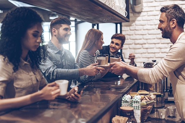Votre commande est prête ! vue latérale du barista passant des tasses de café à son client en se tenant debout au comptoir du bar
