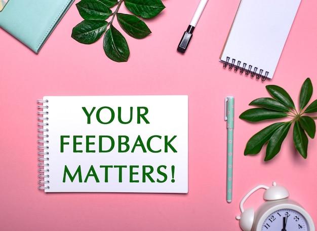 Votre Commentaires Compte Est écrit En Vert Sur Un Bloc-notes Blanc Sur Fond Rose Entouré De Blocs-notes, De Stylos, D'un Réveil Blanc Et De Feuilles Vertes Photo Premium