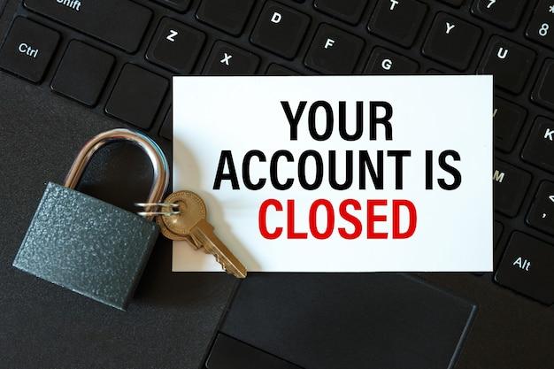 Votre compte est fermé - une inscription sur une carte et un cadenas sur la table par un ordinateur