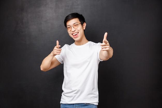 Votre homme rock. joyeux beau jeune mec asiatique assister à une superbe fête louange beau travail, pointant du doigt, recruter une personne rejoindre son équipe, sourire heureux, mur noir
