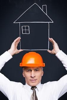 Votre maison est entre de bonnes mains. homme senior confiant en tenue de soirée et casque tenant une maison dessinée à la craie dans ses mains tout en se tenant contre le tableau noir
