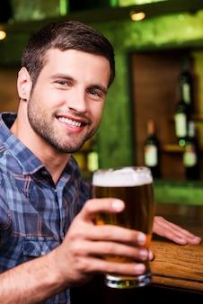 À votre santé! beau jeune homme grillant avec de la bière et regardant la caméra avec le sourire alors qu'il était assis au comptoir du bar