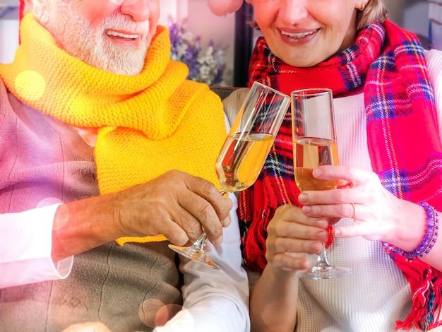 À votre santé! gros plan sur deux personnes âgées tenant des verres de champagne et portant un toast à noël. fête d'événement festif de couple.