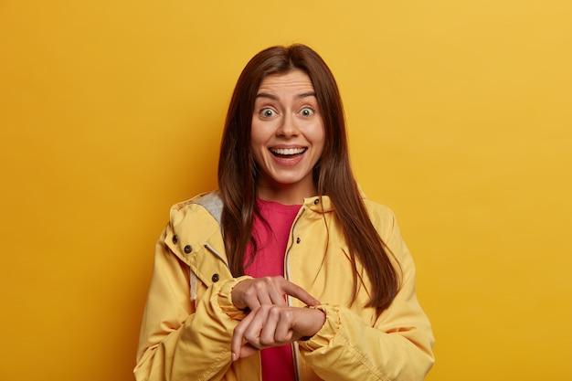 Votre temps est compté. une étudiante positive pointe au poignet, sur une montre invisible, est très ponctuelle et se rencontre à temps
