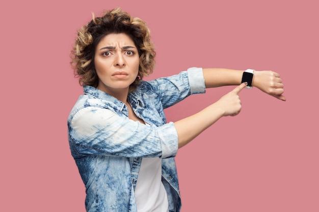 Votre temps est compté. portrait d'une jeune femme autoritaire sérieuse avec une coiffure frisée en chemise bleue décontractée debout et pointant sur sa montre intelligente. tourné en studio intérieur, isolé sur fond rose.