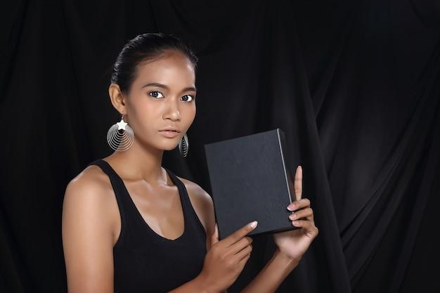 Votre texte différent ici. jolie jeune femme de visage de modèle asiatique tenant une boîte noire de tableau blanc vide. éclairage de studio fond sombre portrait demi-corps copie espace pour la zone publicitaire