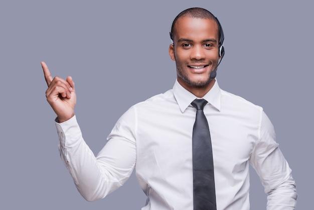 Votre texte ici. confiant jeune homme africain dans le casque pointant vers l'extérieur et souriant
