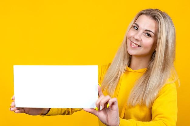 Votre texte ici. jolie jeune femme caucasienne tenant un tableau blanc vide
