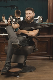 Vous allez adorer mon style! beau barbier barbu dur et viril assis sur une chaise avec une tondeuse à la main et tenant un pistolet winchester et souriant joyeusement