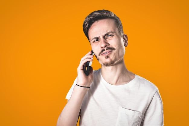 Vous aurez des problèmes homme portrait d'un gars agressif confus en colère parle avec irritation au téléphone