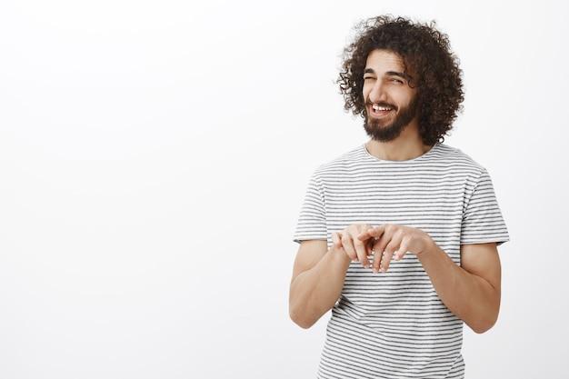 Vous avez couché ensemble, d'accord. portrait d'un ami masculin joyeux intrigué avec coupe de cheveux bouclés et barbe, frottant l'index et riant avec un indice