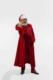 Vous choisir. père noël élégant et moderne en costume à la mode rouge isolé sur fond blanc. on dirait une rock star. nouvel an et réveillon de noël, fête, vacances, humeur hivernale, mode.