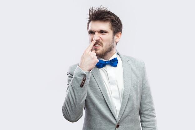 Vous êtes un menteur. portrait d'un bel homme barbu en colère en costume gris décontracté et noeud papillon bleu debout et touchant son nez avec un geste de mensonge. tourné en studio intérieur, isolé sur fond gris clair.