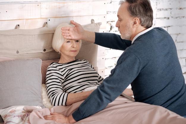 Vous êtes tombé malade. un homme âgé est assis sur le lit près de sa femme allongée et touche son front avec la main.