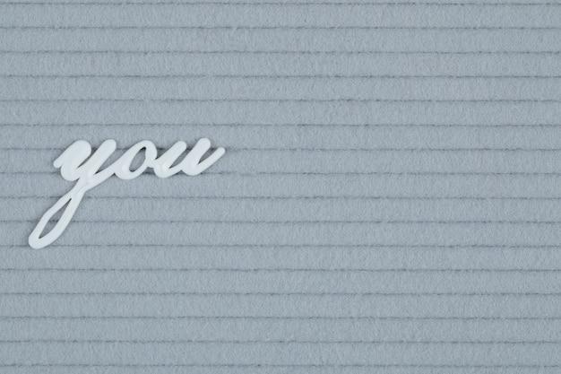 Vous mot incrusté sur une surface grise
