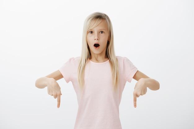 Vous n'en croiriez pas vos yeux. je me suis demandé une fille européenne émerveillée aux cheveux blonds dans un t-shirt rose élégant, pointant vers le bas avec l'index et la mâchoire tombante, disant wow, voyant des choses étonnantes et surprenantes