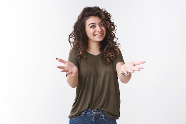Vous voilà. reconnaissante charmante jeune fille aux cheveux bouclés de race blanche vous félicite en remerciant l'aide pointant la caméra bras tendus souriant largement se sentir reconnaissant apprécier chérir ami, fond blanc