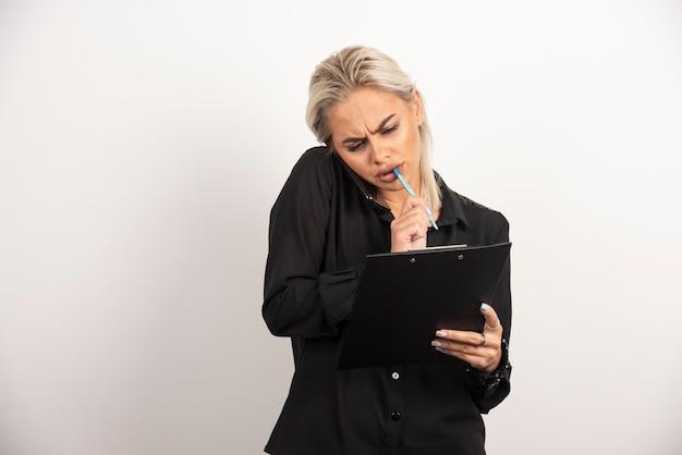 Vous vous demandez femme parlant au téléphone mobile et tenant un presse-papiers. photo de haute qualité
