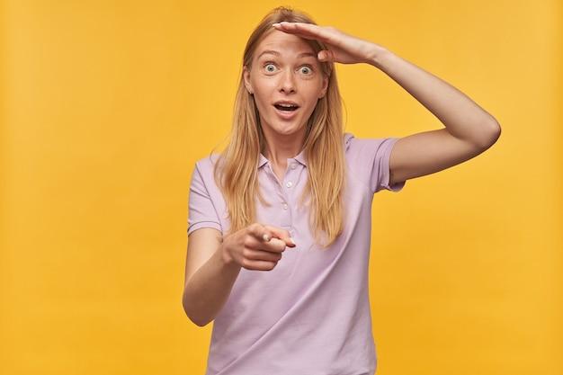 Vous vous demandez jolie jeune femme avec des taches de rousseur en tshirt lavande à la recherche de loin et pointant la caméra sur vous sur jaune
