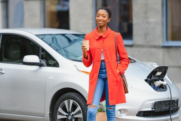 Vous vous interrogez sur les nouvelles technologies. femme sur la station de recharge de voitures électriques pendant la journée.