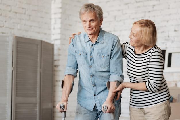 Vous vous sentez bien. admirable bel homme mûr s'améliorant après une blessure et utilisant des béquilles pour marcher pendant que sa femme l'attribue