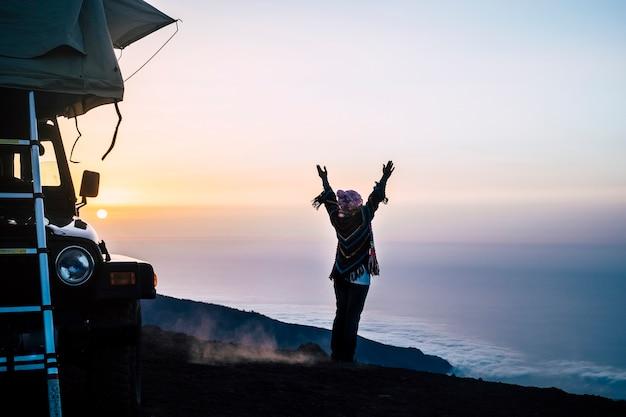 Voyage et activité de loisirs de plein air sauvage avec une femme heureuse devant les nuages et les montagnes au coucher du soleil