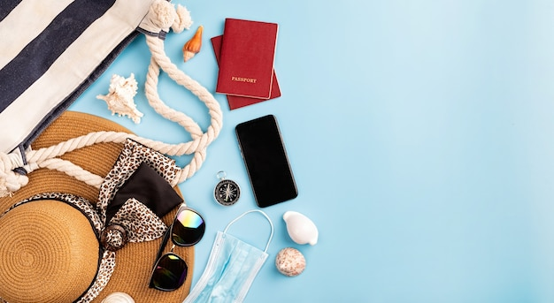 Voyage et aventure objets de voyage à plat avec chapeau d'été, smartphone, passeport, lunettes de soleil et boussole sur fond bleu avec espace de copie