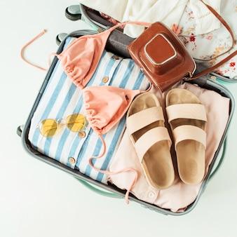 Voyage bagages à main avec maillot de bain bikini, pantoufles, lunettes de soleil, robe, appareil photo rétro sur surface blanche