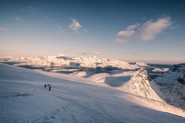 Voyage du groupe de voyageurs sur la colline enneigée au coucher du soleil