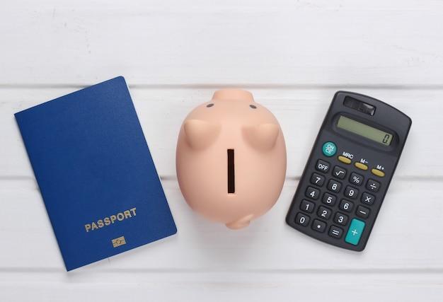Voyage ou émigration. passeport avec tirelire, calculatrice sur une surface en bois blanche. vue de dessus