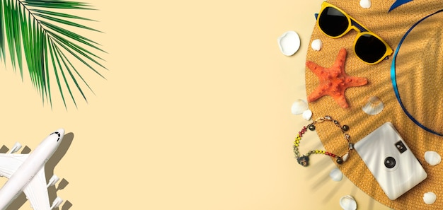 Voyage été fond lunettes de soleil chapeau palmier feuilles tropicales avion et accessoires de plage sur un col...