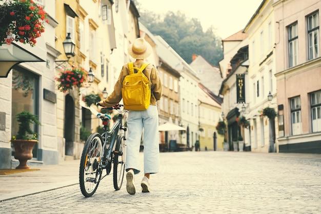 Voyage europe jeune fille avec sac à dos et vélo urbain dans la vieille rue du centre de ljubljana