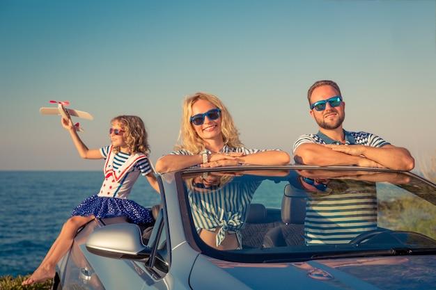 Voyage en famille heureux en voiture les gens s'amusant dans le concept de vacances d'été cabriolet bleu