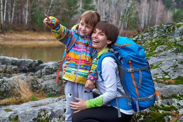 Voyage en famille - la mère et l'enfant avec des sacs à dos rient et pointent du doigt la distance