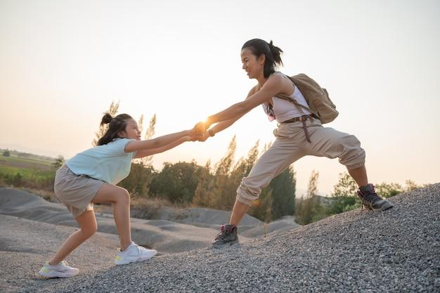Voyage en famille - randonneurs avec sac à dos regardant vue sur les montagnes, mère avec enfant.