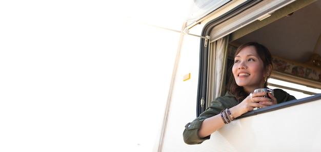 Voyage en famille en voiture caravan sur de belles vacances. jeune femme asiatique en caravane avec une tasse de café blanche le matin