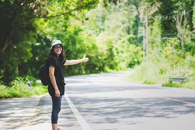 Voyage femme auto-stoppeuse avec chapeau et sac à dos marchant sur une route