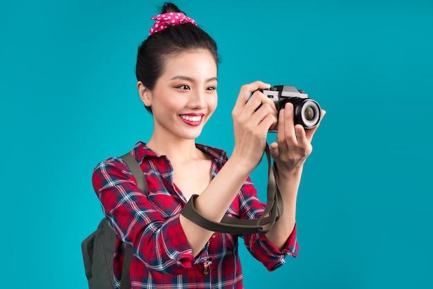 Voyage de femme. jeune belle voyageuse asiatique prenant des photos sur fond bleu
