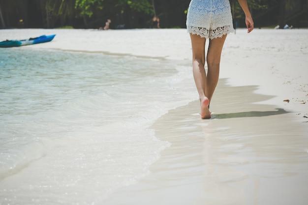 Voyage femme pied sur plage