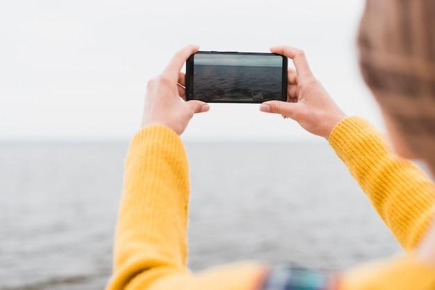 Voyage femme prenant une photo de la mer