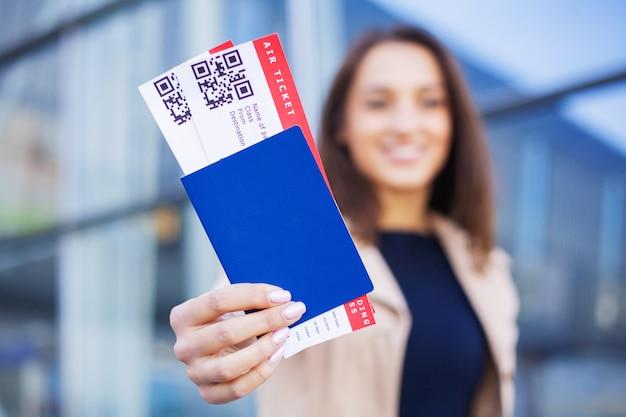 Voyage, femme tenant deux billets d'avion dans un passeport étranger près de l'aéroport