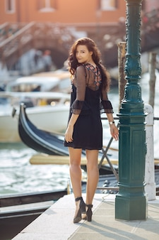 Voyage femme touristique sur la jetée contre belle vue sur le chanal vénitien à venise, italie.
