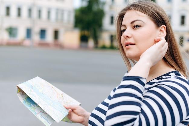 Voyage femme visitant la ville avec la carte dans ses mains et regardant autour.