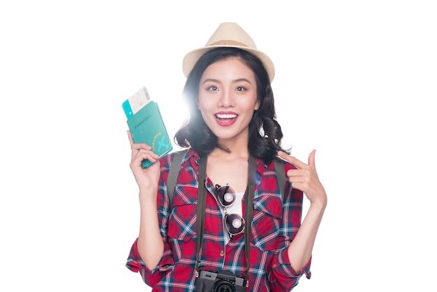 Voyage de femme. voyageur de la belle jeune femme asiatique tenant un passeport et un billet d'avion debout sur blanc.