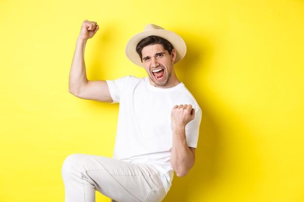 Voyage gagnant de touristes masculins chanceux, se réjouissant et disant oui, faisant le poing de la pompe tout en triomphant, debout contre le mur jaune