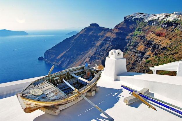 Voyage en grèce. merveilleuses vacances sur l'île de santorin. vue sur la caldeira et vieux bateau en bois