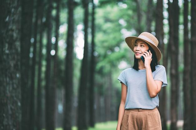 Voyage d'hiver se détendre concept de vacances, jeune femme asiatique de voyageur heureux avec téléphone mobile visites dans la forêt de pins à suan son bo kaeo park, chiang mai, thaïlande