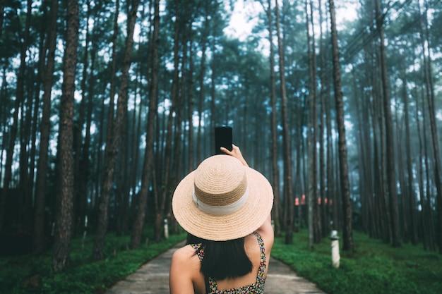 Voyage d'hiver se détendre concept de vacances, jeune femme asiatique de voyageur heureux avec téléphone mobile visites dans le jardin de pins à doi bo luang forest park, chiang mai, thaïlande